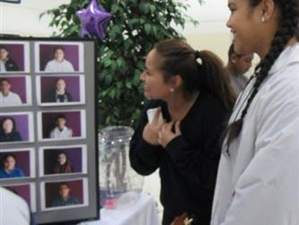 Students view gallery of images of students who received an honor roll award.