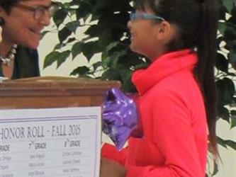girl in pink coat with glasses receives an honor roll award.