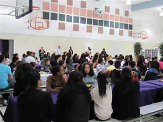 assembly of parents and students that have received honor roll awards sit at cafeteria tables eating.