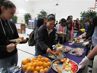 Parents and students at the buffet line serving themselves fruit.