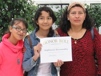 Parent with two children holding Honor Roll Certificate