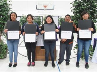 Five students showing their honor roll awards.