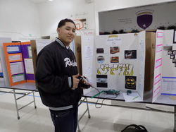 Male student presenting his project at the Science, Technology, Engineering, and Math fair.